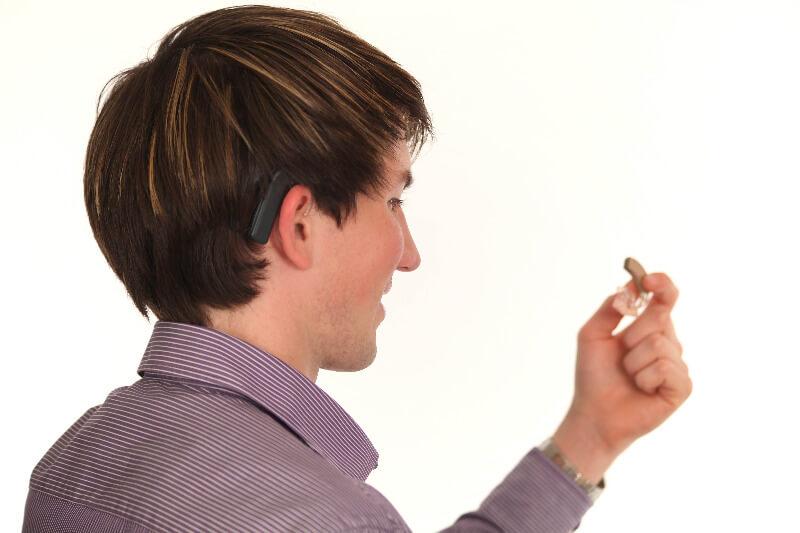 Signalhund für schwerhörigen Mann, der sein Hörgerät in der Hand hält